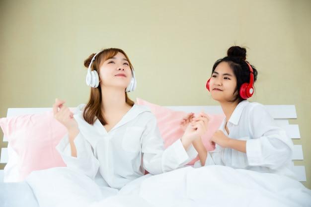Beste vrienden blij met het luisteren lied in slaapkamer Gratis Foto
