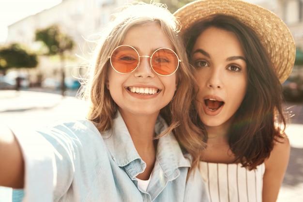 Beste vrienden dragen een stijlvolle outfit en nemen selfie op straat Gratis Foto