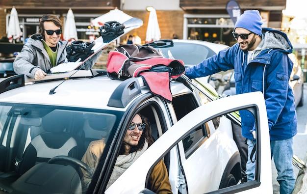 Beste vrienden plezier samen en auto voorbereiden voor ski en snowboard op bergtocht Premium Foto