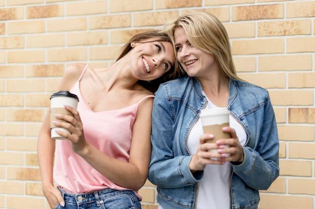 Beste vrienden poseren met hun kopjes koffie Gratis Foto