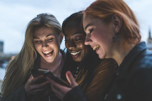Beste vriendenmeisjes met smartphones het lachen Premium Foto