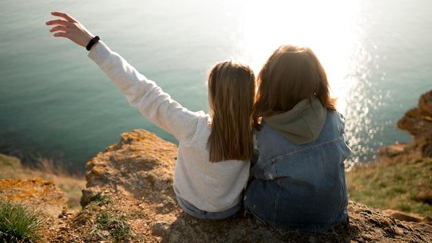 Beste vriendinnen elkaar en oceaan knuffelen Gratis Foto