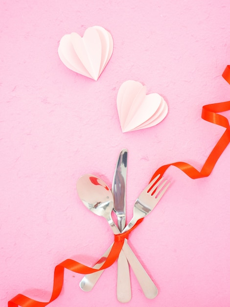 Bestek en harten op roze tafel Premium Foto