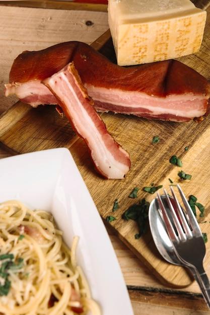 Bestek en pasta in de buurt van vlees en kaas Gratis Foto