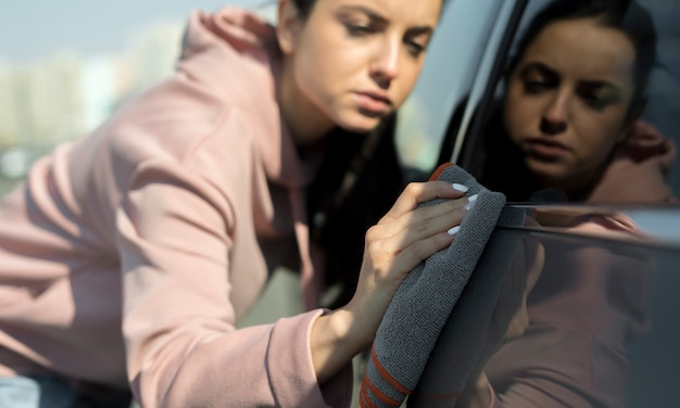 Bestuurder die voor haar auto zorgt en deze schoonmaakt Gratis Foto