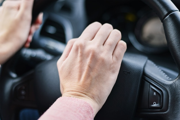 Bestuurder hand ingedrukt claxon op auto wiel Premium Foto