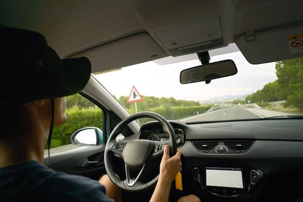 Bestuurder reist in zijn auto op de snelweg, uitzicht vanuit de auto. handen aan het stuur, koud zomerweer Gratis Foto