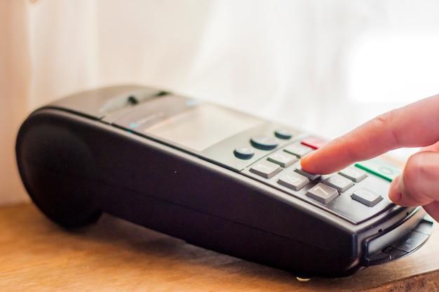 Betaling met creditcard - zakenman bedrijf pos terminal. betalingskaart in een bank terminal. het concept van elektronische betaling. hand pin code op pin pad van kaart machine of pos terminal Gratis Foto