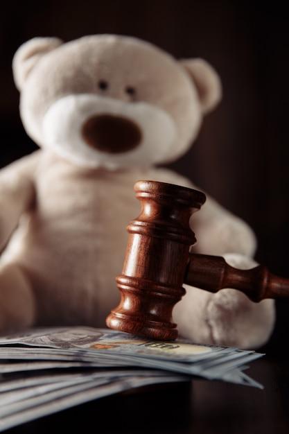 Betalingen alimentatie. houten rechterhamer, geldbankbiljetten en teddybeerclose-up. echtscheiding concept. Premium Foto