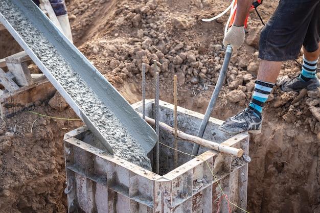 Beton gieten in stalen kist voor funderingspijler tijdens woningbouw Premium Foto