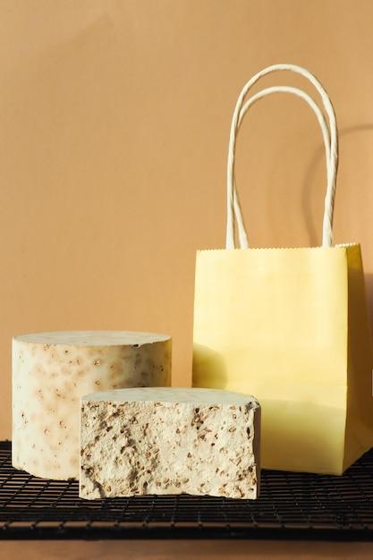 Betonnen podiumcilinders en een papieren zak op een zwart rooster. kopieer ruimte. Premium Foto