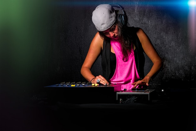 Betoverend meisje deejay aan het werk dat geluid op haar console bij ap mengt Premium Foto