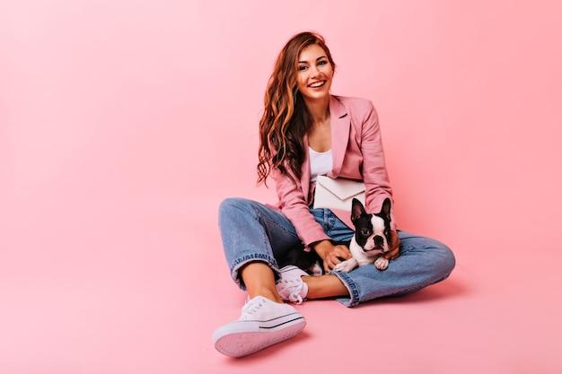 Betoverend meisje in het witte sportschoenen poseren met hond. lachende aantrekkelijke vrouw zittend op de vloer met schattige bulldog puppy. Gratis Foto