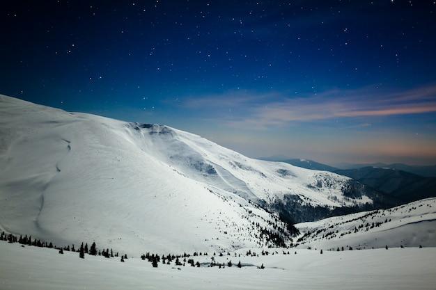 Betoverend mooi uitzicht op de bergen en heuvels in de besneeuwde vallei in de late avond Premium Foto