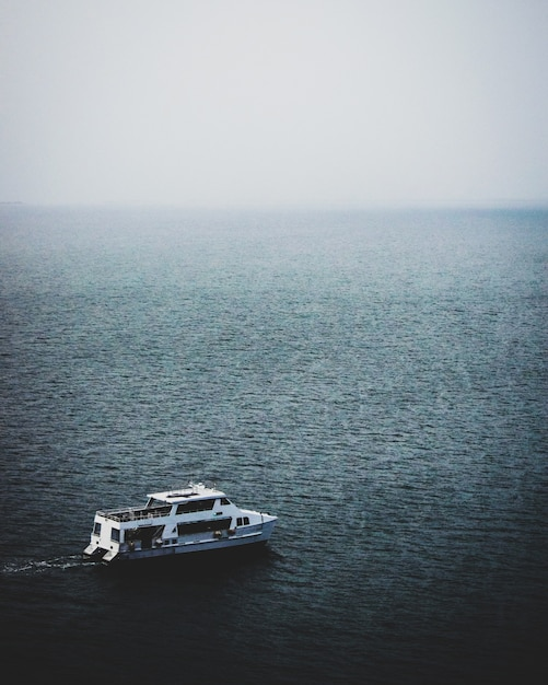Betoverend uitzicht op de boot in de kalme zee op een mistige dag Gratis Foto