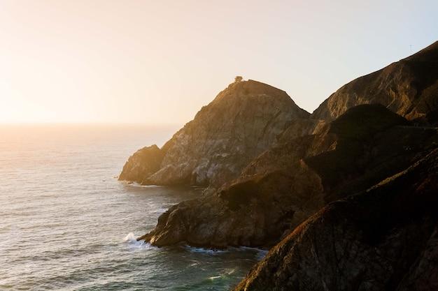 Betoverend uitzicht op de kalme oceaan en de kliffen aan de kust onder de blauwe lucht tijdens zonsondergang Gratis Foto