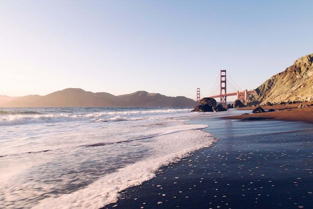 Betoverend uitzicht op de kalme oceaan met de brug en de bergen op de achtergrond, vs. Gratis Foto