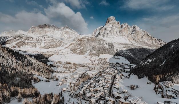 Betoverend uitzicht op een kleine stad in de winter, omringd door rocky mountains bedekt met sneeuw Gratis Foto