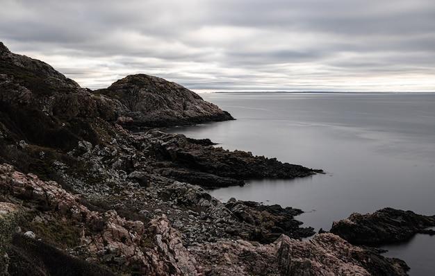 Betoverend uitzicht op een rotsachtige kust en een kalme zee op een sombere dag Gratis Foto