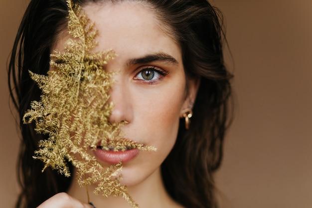 Betoverend wit meisje met trendy sieraden poseren met plant. close-up shot van verbaasd vrouwelijk model met gouden accessoires en groen blad. Gratis Foto