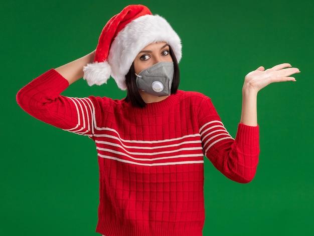 Betrokken jong meisje met kerstmuts en beschermend masker kijken camera hand houden op het hoofd met lege hand geïsoleerd op groene achtergrond Gratis Foto