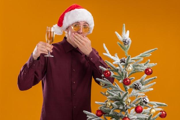 Betrokken jonge blonde man met kerstmuts en bril staande in de buurt van versierde kerstboom op oranje achtergrond Gratis Foto