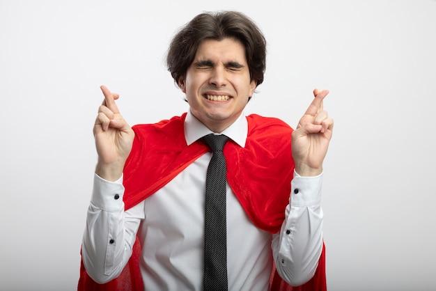 Betrokken jonge superheld man met gesloten ogen dragen stropdas kruising vingers geïsoleerd op wit Gratis Foto