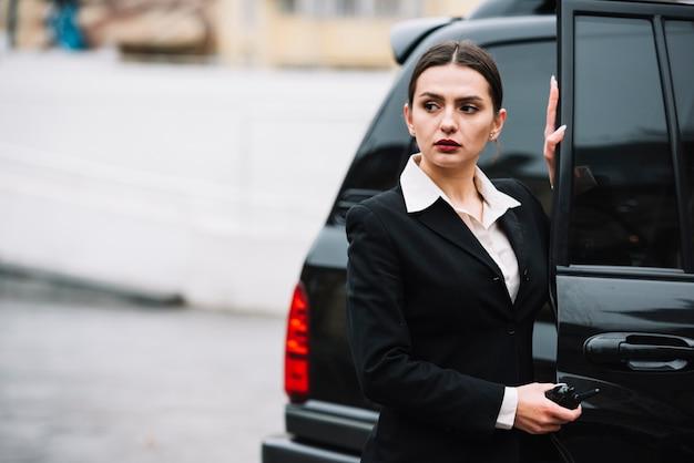 Beveiliging vrouw opening auto voor clientt Gratis Foto