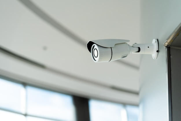 Beveiligings witte cctv-camera (gesloten televisiecircuit) in het kantoorgebouw Premium Foto