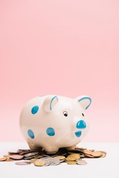 Bevlekte ceramische piggybank over muntstukken tegen roze achtergrond Gratis Foto