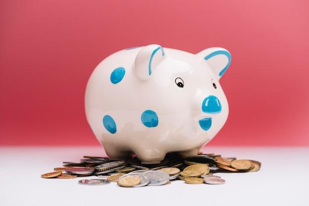 Bevlekte ceramische piggybank over muntstukken voor rode achtergrond Gratis Foto
