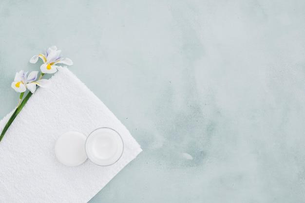 Bevochtigende room en bloem op handdoek met exemplaarruimte Gratis Foto