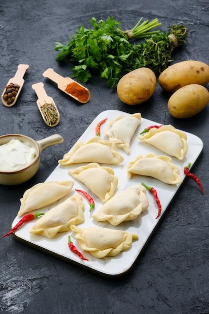 Bevroren aardappelvareniki op marmeren dienende raad met ingrediënten Premium Foto