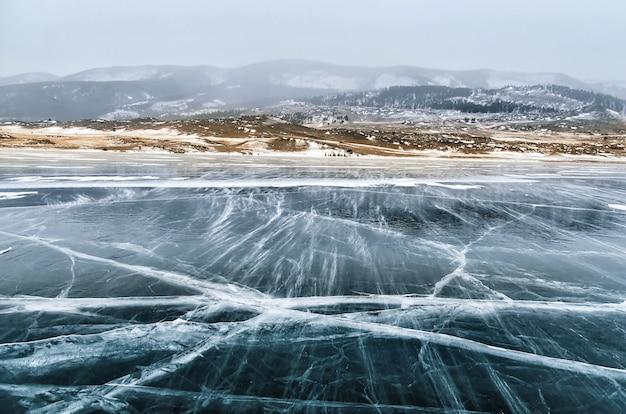Bevroren baikalmeer. prachtige berg in de buurt van het ijs oppervlak op een ijzige dag. Premium Foto