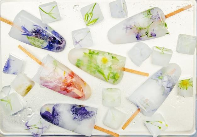 Bevroren bloemen in ijsblokjes en ijs op een stok. selectieve aandacht. Premium Foto
