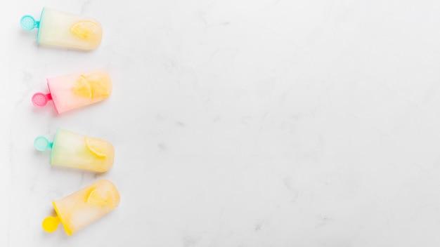 Bevroren ijsijslolly met citrusvrucht op kleurrijke stokken Gratis Foto