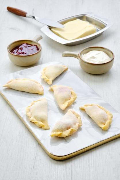 Bevroren kersenvareniki op marmeren dienende raad met ingrediënten Premium Foto