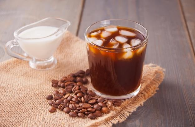 Bevroren latte koffie met ijsblokjes en koffiebonen op een tafel. Premium Foto