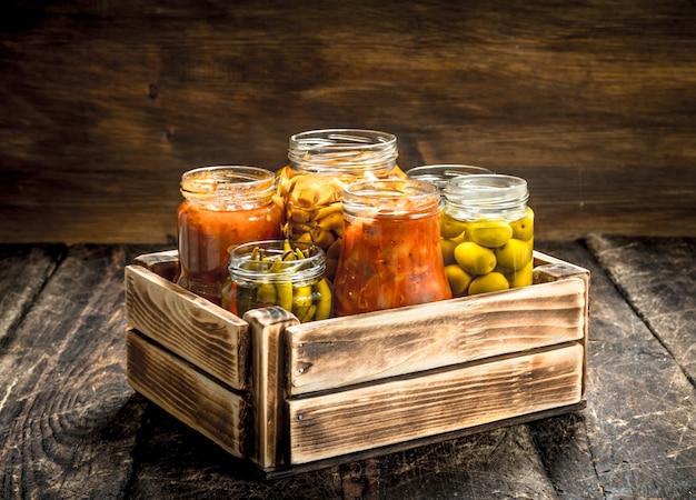 Bewaart champignons en groenten in een doos. op een houten tafel. Premium Foto