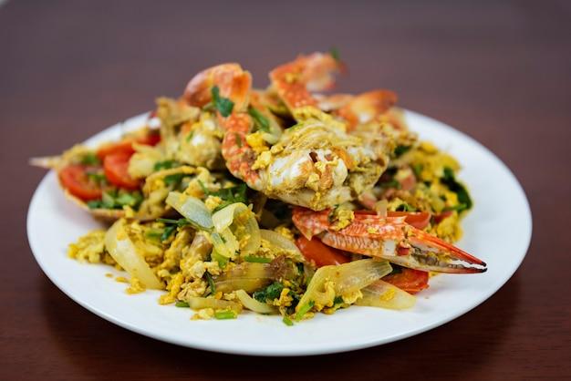 Beweeg gebraden krab met kerriepoeder, close-up, thais voedsel op een houten achtergrond Premium Foto