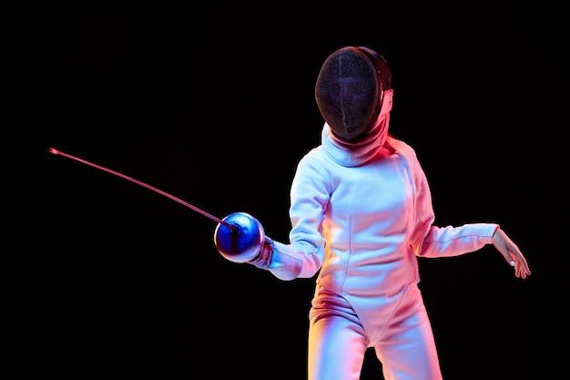 Beweging. tienermeisje in hekwerkkostuum met in hand zwaard geïsoleerd op zwarte muur, neonlicht. jong model oefenen en trainen in beweging, actie. copyspace. sport, jeugd, gezonde levensstijl. Gratis Foto