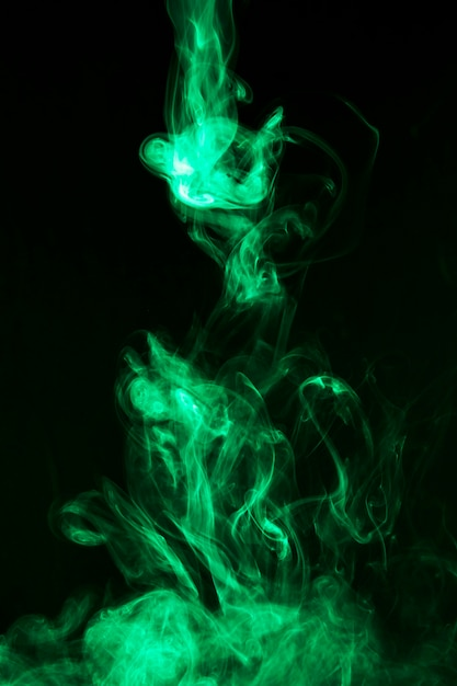 Beweging van heldergroene rook op zwarte achtergrond Gratis Foto