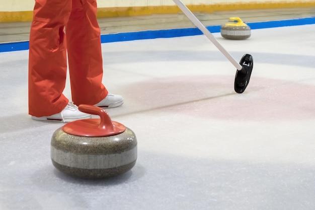 Bezem en steen voor curling op ijs van een indoor ijsbaan. Premium Foto