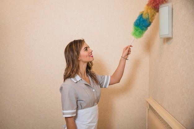 Bezig meisje die de muurlichten met kleurrijke stofdoek schoonmaken Gratis Foto