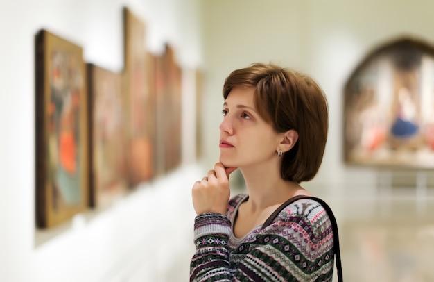 Bezoeker zoekt foto's in de kunstgalerij Gratis Foto