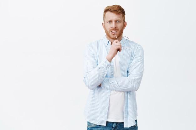 Bezorgd gefocuste aantrekkelijke blanke man met rood haar en borstelharen bijt op de rand van een bril terwijl hij zenuwachtig staart, nadenkt over problemen, probeert het in gedachten op te lossen, uitweg zoekt Gratis Foto