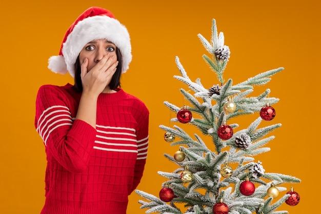 Bezorgd jong meisje met kerstmuts staande in de buurt van versierde kerstboom hand op mond houden een ander achter rug kijken camera geïsoleerd op een oranje achtergrond Gratis Foto