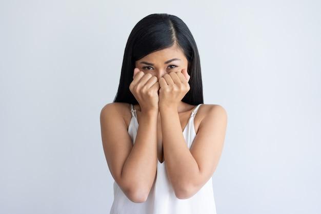 Bezorgd jonge aziatische vrouw die mond achter vuisten Gratis Foto