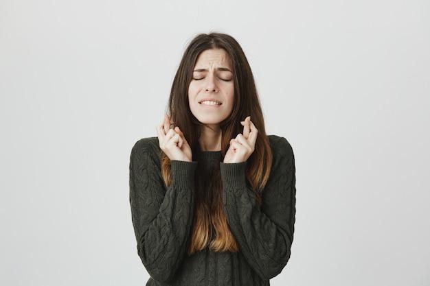 Bezorgd jonge leuke vrouw die wens met gesloten ogen en gekruiste vingers Gratis Foto