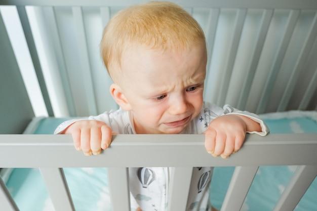 Bezorgd schattige baby staande in wieg, leuning vasthouden, huilen en wegkijken. close-up shot, hoge hoek. kinderopvang of jeugdconcept Gratis Foto
